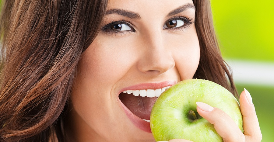 Close-up photograph of a women with brown eyes and brown hair smiling while biting into a green apple.