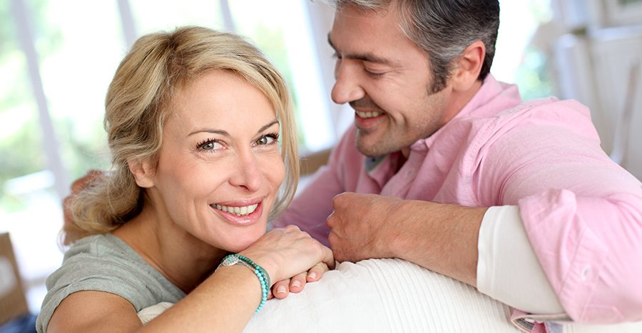 Photograph of a blonde woman and a man smiling while in a home setting.