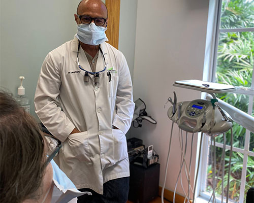 Dr. Larry Saylor consulting with patient sharing recommended dental plan to have healthy teeth and gums